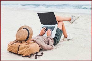 Парень на пляже за компьютером